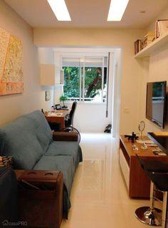 Superpequena, esta sala conseguiu ainda um espaço para o home office. As cores de madeira dos móveis contrastam com o branco do ambiente, dando aconchego e estilo