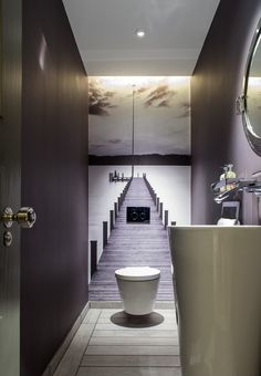 half bathroom with grey painted wall, wallpaper with long bridges picture in the back, white toilet, white long round sink of Clever Ideas for Beautiful Minimalist Half Bathroom