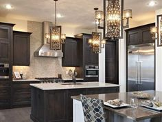 This transitional island-shaped kitchen layout with modern finishes features black cabinets with beige & mocha wall accents. Transitional Living Rooms, Transitional House, Transitional Lighting, Furniture Layout, Kitchen Furniture, Kitchen Layouts With Island, Island Kitchen, Cool Light Fixtures, Houses Architecture