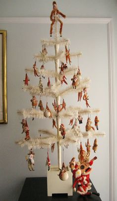 """White """"feather tree"""" with old Santas on it."""