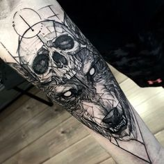A skull and wolf themed sleeve tattoo. You can see the human skull being used as a hat by the angry looking wolf. The tattoo looks well done and fearless and definitely not for the weak of will.