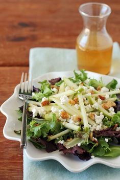 This Harvest Apple Salad is light, fresh & perfect for Fall with creamy goat cheese, earthy walnuts, tart Granny Smith apple and an Apple Cider Vinaigrette! Just 136 calories or 5 Weight Watchers SmartPoints. www.emilybites.com