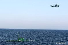 A helicopter and submarine are seen during Iranian naval maneuvers dubbed Velayat 90 on the Sea of Oman, Iran, Dec. 27, 2011. The Iranian Navy launched 10-day massive naval exercises in the international waters on Saturday. The naval drills, dubbed Velayat 90, cover an area of 2,000 km stretching from the east of the Strait of Hormuz in the Persian Gulf to the Gulf of Aden. (Xinhua/Stringer/Ali Mohammadi)