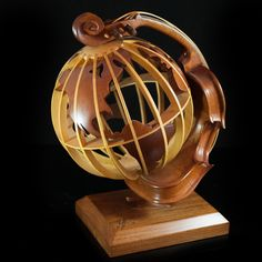 """Lot #120: Phillippe Guillerm(American 1959-) Wood Sculpture  DESCRIPTION: Wooden sculpture by Phillippe Guillerm. Expressionist sculpture of a violin bent around a wooden globe. The globe spins and swivels with the violin placed as the axis. Neck of violin has broken off. Signed: """"Guillerm"""" on the base.  CIRCA:20th ORIGIN:USA DIMENSIONS:H: 17″ L:14.5″ W:11″"""
