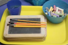 """The children each got a chalk board. I wrote their name on their board. They each got a wet paintbrush and """"painted"""" over the letters of their names. This activity helps develop their fine motor skills as they practice writing their names."""