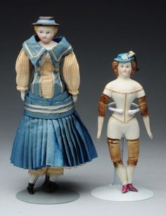 Shoulder head with blonde hair and molded black hat (several touched up chips on rim) with blue ribbons coming down back of head onto shoulder plate which also has a molded blouse with white china finished collar and lavender bow, painted features (cheek rub, several making dents on forehead), antique cloth body with bisque lower limbs, original outstanding blue and white silk dress and undies (some deterioration on skirt, fading). Rare partly bisque doll with molded underwear on torso…