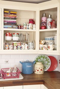 Love the butcher-block counter top and open cupboards with colorful dishware.