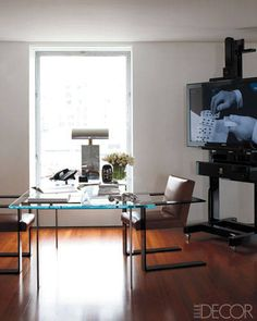 In the living room alcove, the television stand is a copy of an easel found in Paris and the desk is by Ralph Lauren Home.   - ELLEDecor.com