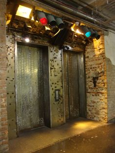 "These interesting elevators are located at Chelsea Market in Manhattan (New York City).  The elevators, named ""Elevator Bank"", are surrounded with safety deposit boxes. Old traffic signals are also used for lighting to give a really neat effect while waiting for the next elevator."