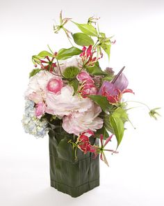 Arrangement is composed of pink roses, blush peonies, tulips, paper whites, gloriosas, lilac, hyacinth,& ranunculus. Vase wrapped in cecropria & aspidistra leaves. Make sure to clean your vase thoroughly with bleach & water, as bacteria can shorten the life of a flower dramatically -- roses are particularly sensitive. Change water every day. If you do not have access to flower food,fill 1/4 of vase w/lemon-lime soda and the rest with cold water.(Takashimaya, Japanese specialty store NY)