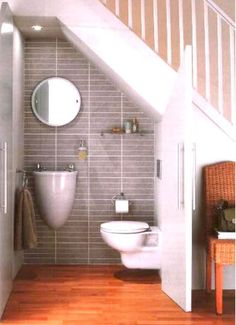Installing a powder room under the stairs is a great use of typically wasted space. This particular image is one of my favorites, and part of what makes it work is the small wall mounted sink that frees up floor space in front of the toilet.