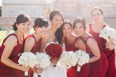 Stunning bridal party in their crimson dresses and white bouquet vs the bride in white with a crimson bouquet!