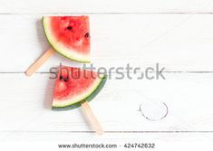 Watermelon popsicle on wooden white background. Watermelon slices on sticks. Top view, fat lay.