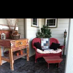 Cozy corner on the porch... I like the small love seat angled on the corner. And wicker. I love wicker.