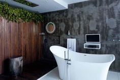 Banheira retrô, na Heaven, parede com ripas de madeira ipê petrificada de Bali e espelho e acessórios importados de Hong Kong (Foto: Filippo Bamberghi)