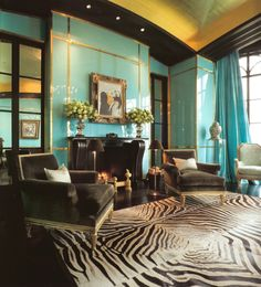 I love how the curtains match the turquoise lacquer walls. The pieced-together zebra rug is also beautiful and is that a Picasso over the fireplace?