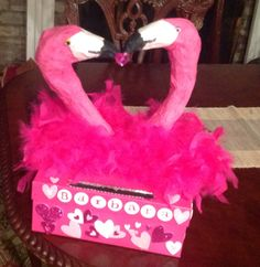 Flamingo valentine box. Heads made with paper towel tubes and crepe paper. Body, paper ball covered with feather boa.