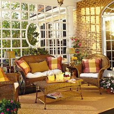This 35-foot-long by 9-foot-deep back porch respects Southern porches of the past by using traditional shading devices such as a trellis at one end. Comfortable rattan chairs, cushioned in red, yellow, and green, add cheer to this outdoor living room. Ceiling fans help cool the space during sultry summer days, while three copper-finish lanterns contribute to the ambience. Lovely!