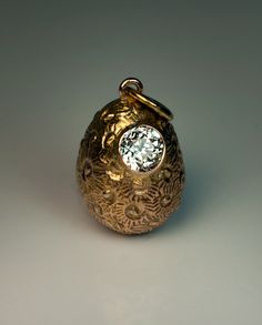 A Russian Solitaire Diamond and Gold Egg Pendant made in St. Petersburg between 1904 and 1908. The textured 14K gold egg is set with a sparkling old European cut diamond.
