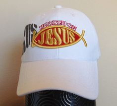 "This white baseball cap features the message ""Hooked on Jesus"" embroidered in…"