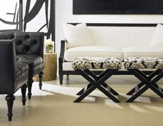 Classical touches in an eclectic mix team the Morris sofa upholstered in white and trimmed with nailheads, X-stools with a patterned black-a...
