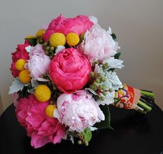 Trendy and tropical bouquet of peony, craspedia and dusty miller. Different colors though