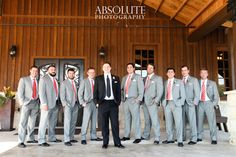 Groomsmen in gray and coral, groom in classic black.  Photo by Absolute Photography, Floral by Petals Couture.
