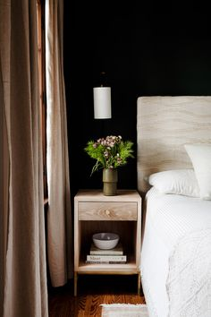 Black walls in bedroom with neutral curtains and pretty floral arrangement on bedside table