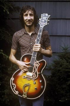Pete Townshend and his guitar. He should smile more often, he has such a nice smile and lights up in this photo