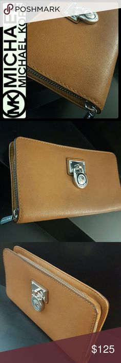 Michael Kors Leather Zipper Wallet Michael Kors Signature Brand in Classic Pebbled Brown Leather! Zipper Around Style and Add Chic to Your Take-Everywhere Essentials! Multi Pocket Crafted from Luxurious Leather with Silver Tone Hardware!  Features MK Logo Emblem Medallion atty The Front, Interior Has Zipped Pocket for Coins, Multiple Slots for Bills, 10 Cards Slots! Approx Size 8x4.5 inches, Used in Mint Condition! Michael Kors Bags Wallets