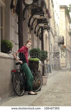 beautiful girl with a bicycle on the streets of the beautiful city
