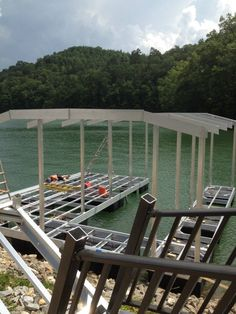 North Georgia Boat Lift & Marine Construction Company completed work on a brand new CAT 5 dock earlier this week. This dock, installed at Lake Fontana, features a standard single-slip combined with a wide-side to house the owner's boat. Ironwood decking was used in the construction of the main dock, the gangway also sporting it. Wahoo bumpers line the inside of the slip, protecting the boat from any damage. The upper level consists of a deck and roof. Boat Lift, Decking, Blue Ridge, Garden Bridge, Maine, Georgia, Construction, Outdoor Structures, Cat