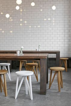 white tile + chunky wood tables + wood/painted stools + concrete floors: