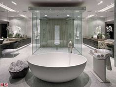 Check out this totally contemporary bathroom with white circular tub and square glass shower.  See more images of this very special home on realtor.com.