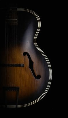 Gorgeous photo of an archtop guitar. Love the lighting, the composition, and the transition between the sunburst and the black background. Even the reflection of the light source is in the perfect spot, balancing the sound hole below it. Wow!