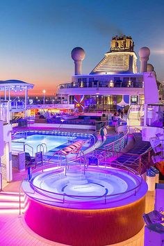 See cruise ships light up as the day winds down. Anthem of the Seas glows neon purple on the pool deck.