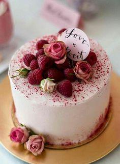 gâteau d'anniversaire au glacage en couleur rose avec des framboises sur le dessus et décoré de vraies roses
