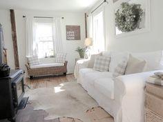 Ikea Ektorp sofa, blekinge white, beige cowhide rug, white & wood, neutral living room, black wood stove.