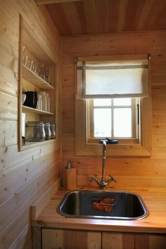 Tiny house kitchen sink.  Good use of storage space and cute little window.