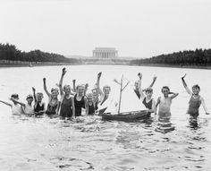 Due to the failure of congress to appropriate money for public pools in Washington a group of boys are seen waving at the photographer while playing in the reflecting pool in front of the Lincoln Memorial with a toy sailboat on July 7, 1926.