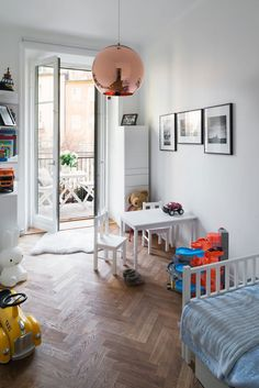 Chic and Colourful Stockholm Apartment - NordicDesign // All white kids room with little pops of colours, gorgeous herringbone hardwood floors and a walkout to a balcony!
