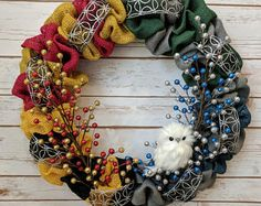 Calling all Harry Potter fans! This Harry Potter inspired wreath features all four house colors with an adorable fluffy owl perched in a bed of shiny baubles. One quarter of the wreath is designated to each of the four houses. Deco Noel Harry Potter, Cadeau Harry Potter, Objet Harry Potter, Harry Potter Bricolage, Décoration Harry Potter, Harry Potter Thema, Fans D'harry Potter, Harry Potter Classroom, Anniversaire Harry Potter