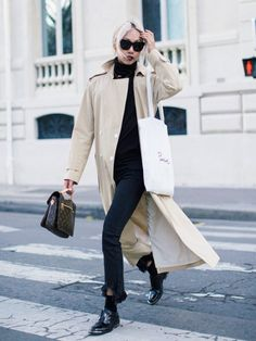Vanessa Hong of The Haute Pursuit wearing a trench coat over black frilled-hem jeans, a black roll neck and patent flats.