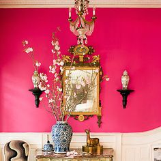 A hot pink wall with traditional gold accents, we love it!