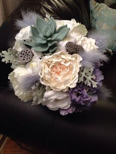 Silk roses, ponies, dusty miller, hydrangea , & succulents with grey feathers and pods