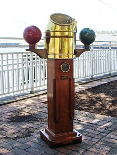 This highly desirable early 20th century binnacle was manufactured by Henry Browne & Son (Sestrel Trade Mark) ltd. is a an exceptional example of the manufacturers instrument. This antique marine ship's Binnacle was deck mounted and features a mahogany pedestal with brass helmet style cover, round sight glass and burner mount over original gimbal compass. The compass is flanked by red and green painted cast iron compensating spheres.
