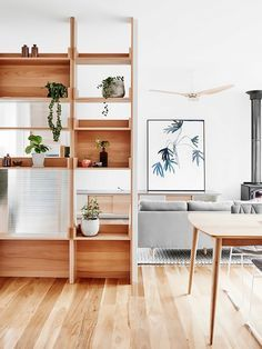 Glass paneling on a floor-to-ceiling bookcase adds a subtle extra layer of separation. We especially love the way the empty shelves allow a space to breathe. Keep styling simple and edited.