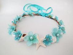 A mermaid's dream is this sweet and ocean inspired flower crown!This beautiful sea shell studded beach wedding flower crown begins with a coated brown floral wire which resembles a natural twig or small branch. This is  covered with small aqua colored  blossoms combined with a variety of lovely little treasures from the sea including  tiny (real) sea shells and star fish and some lovely artificial pearls all in white and ivory colors. The halo is a full crown and is therefore a one size...