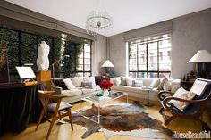 """The Thom Filicia sofa beside the antique scroll-arm chair is long enough to double as a guest bed. Carretero says, """"In small spaces, you have to go with some large pieces. A mix of big and small keeps things interesting."""""""