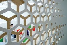 Cutout partitions of birch plywood and MDF outside a classroom create filtered…